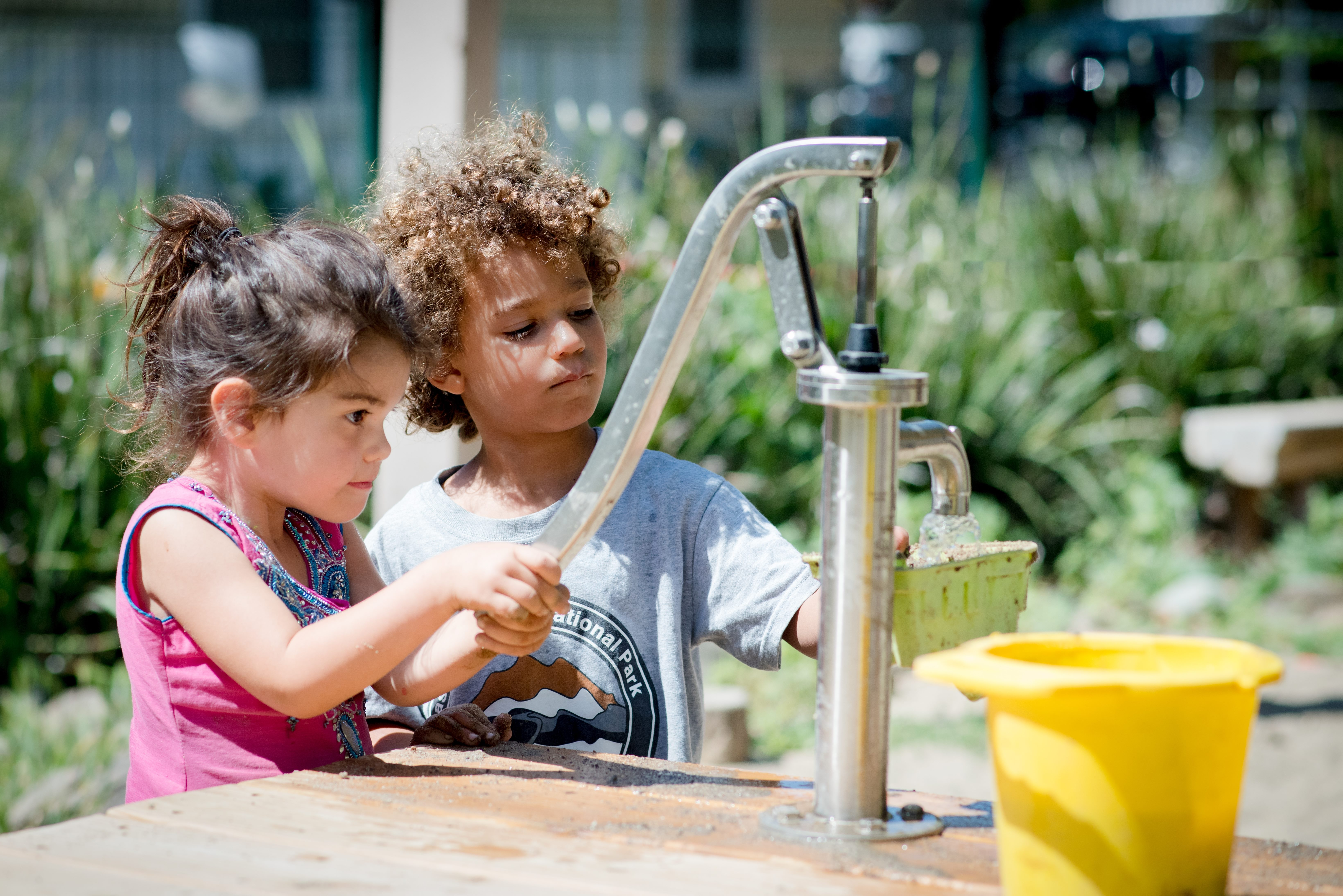 preschoolers pump water together